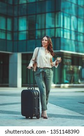 A young woman is going on a business trip through the office district against urban city background and carried a suitcase with her.