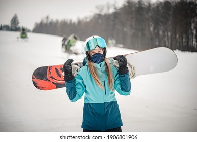 Young woman going snowboarding with nano face mask. Wearing blue sportswear.