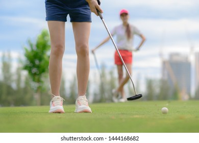 young woman golf player putting golf ball into the hole on the green of the golf course,  an opponent or competitor stand waiting in background