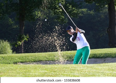 Young woman golfer chipping golf ball out.