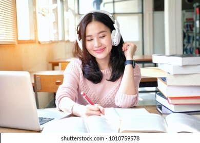 Young woman in a good mood listening to music  while studying in a library