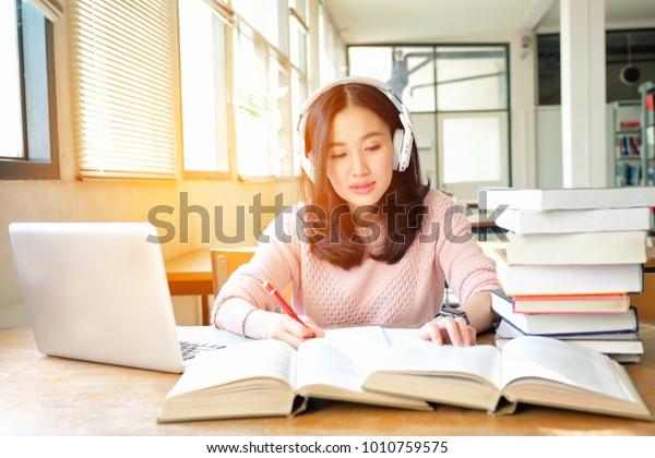 Joven de buen humor escuchando música mientras estudia en una biblioteca