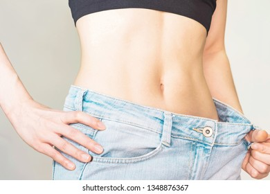 Young woman with good shape Small waist and abdominal muscles Wearing large jeans, she slim down.