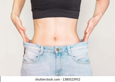 Young woman with good shape Small waist and abdominal muscles Wearing large jeans, she slim down