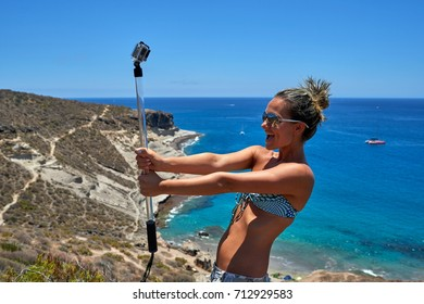 young woman with gopro camera on mediterranean coast in summer