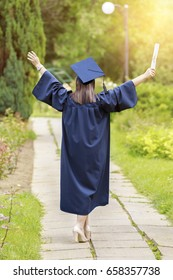 Young woman graduate put her hands up and celebrating with certificate in her hands and feeling so happiness