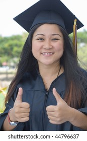 Young woman with graduation cap and gown with thumbs up hand gesture