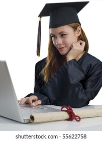 Young woman with graduation cap and gown using notebook computer