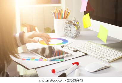 Young woman graphic designer using graphic tablet to do his work at desk