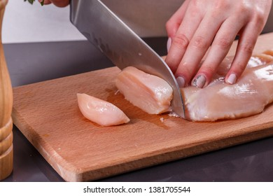 young woman in a gray apron cuts chicken breast