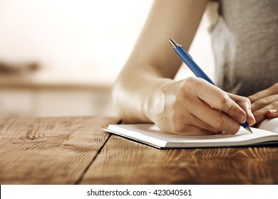 young woman in gray color and blue pen and worn old desk