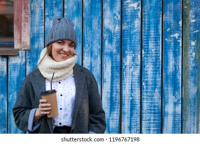 A young woman in a gray knitted hat, gray coat and bluesses enjoys city, poses and drink coffee to go around blue wall. The concept of livestyle and outdoor recreation in autumn