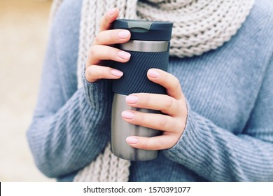 Young woman in a gray sweater thermos thermo cup outdoor portrait. Winter. Details. Cozy.