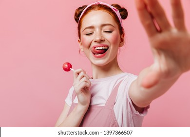 Young woman in great mood licks her lips and holds candy on pink background