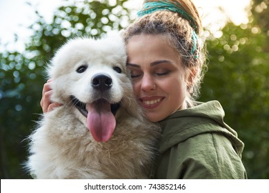 young woman in green coat and multicolored dreadlocks with her white Samoyed dog posing for a picture with closed eyes in autumn Park