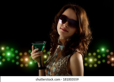 young woman with a green cocktail on a black background