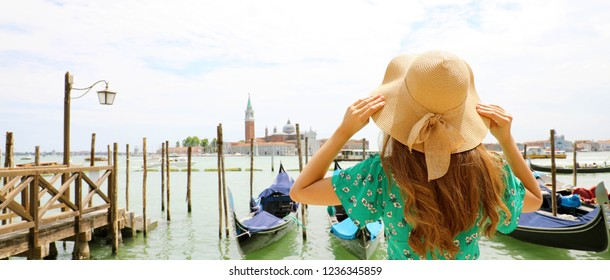 Young woman with green dress holding her hat when looking to Venice Lagoon. Panoramic banner view of traveler girl in Venice, Italy.