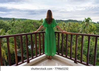 Young woman in green dress is standing on balcony in tropical country and look forward on jungle