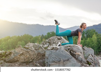 Young woman in green leggins doing the donkey kick exercise on all fours arching back straightening leg up. Concept sport, fitness, lifestyle. Work out and warm up outdoors in mountains near river.