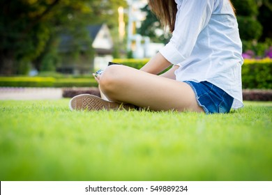 Young woman green nail and white coats relax sitting on grass.