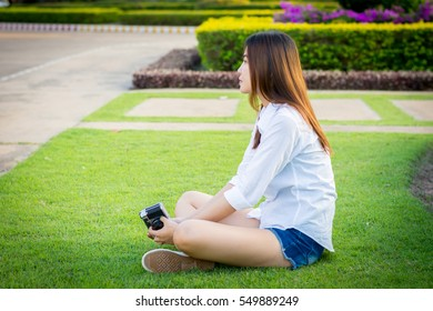 Young woman green nail and white coats relax sitting on grass. And hold vintage camera.
