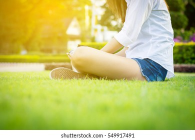 Young woman green nail and white coats relax sitting on grass.  Vintage tone.