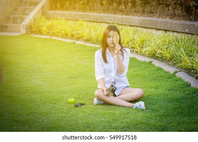 Young woman green nail and white coats relax sitting on grass. And hold vintage camera.  Vintage tone.