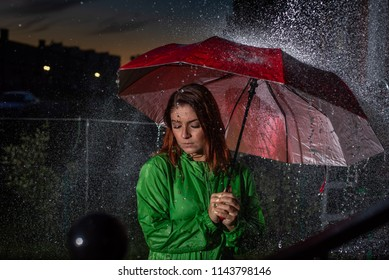 Young woman in green raincoat in rain with red umbrella at night. Sad young woman in the rain with umbrella in the evening. Beautiful woman with red umbrella in lanterns and rain drops