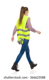 Young woman in green reflective vest, jeans and black boots walking, Rear view. Full length studio shot isolated on white.