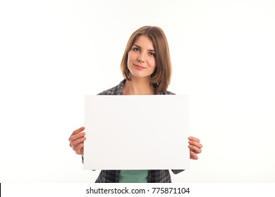 Young woman in green shirt holding sheet of paper and looking at camera. White background is not isolated.