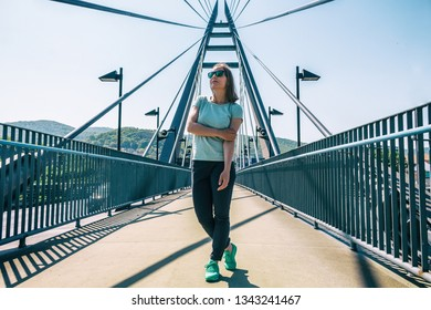 Young woman in green sneakers and sunglasses standing on suspension bridge. Marian bridge at summer sunny day, Usti nad Labem, Czech Republic.