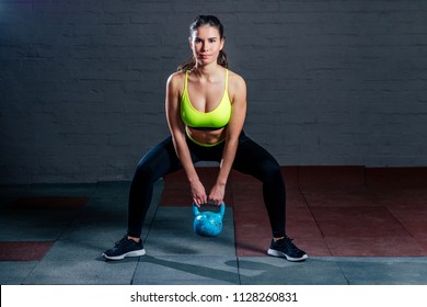 a young woman in a green sports bra and black pants trains with a weight on the background of black bricks