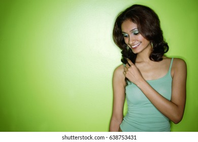 Young woman in green tank top, looking down