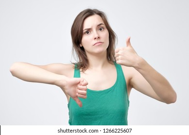 Young woman in green t-shirt showing thumbs up and down sign, choice yes or no
