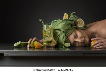 Young woman in green turban with lemons , limes and rosemary on dark background . Copy space for your text .