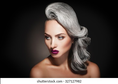 young woman with grey hair color and beautiful makeup in studio on black background