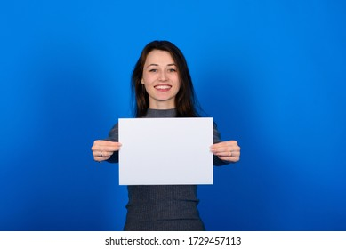 Young woman in grey shirt holding a sheet of paper and looking at the camera, smile. Blue background isolated