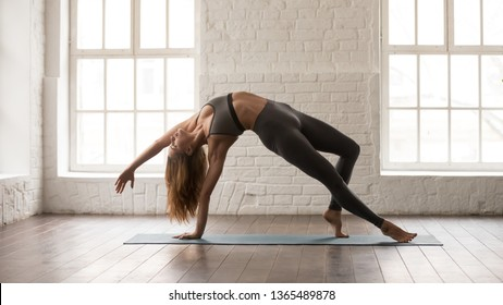 Young woman in grey sportswear, pants and bra practicing yoga, standing in Wild Thing pose, attractive girl doing Camatkarasana exercise, working out at home or in modern yoga studio