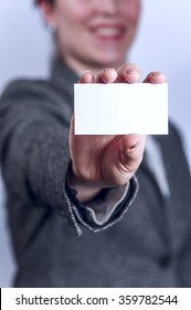 Young woman in grey suit holds business card
