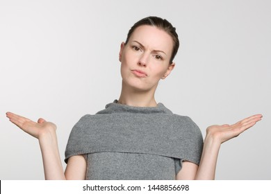 young woman in grey sweater makes a not know gesture with her arms