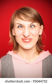 young woman grimacing with crossed eyes in front of red background
