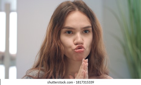 Young woman grimacing face and looking to mirror in bath room. Portrait smiling woman making faces front mirror while facial gym. Positive people emotions concept