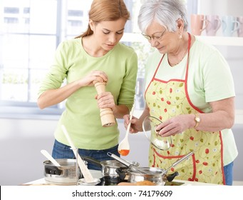 Young woman grinding pepper on food prepared by senior mother.?
