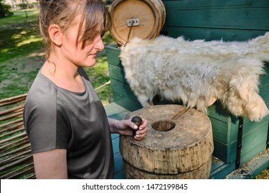 Young woman grinds flour by hand mills. Retro millstone for grinding grain and corn