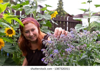 Young woman grooms her plants in the garden