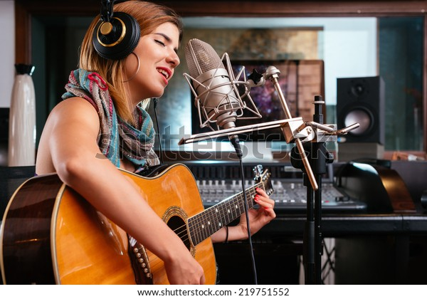 Young woman with guitar recording a song in the studio