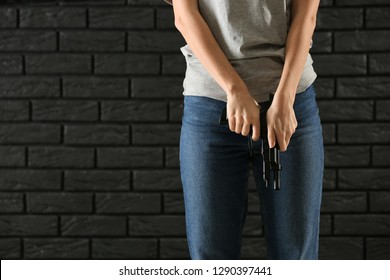 Young woman with a gun on dark brick background