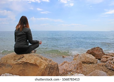 Young woman in gyan mudra on the rocks. Sea is the background.