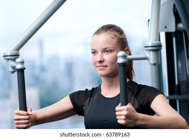 Young woman at the gym exercising on a machine