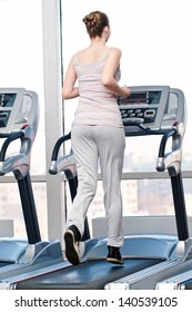 Young woman at the gym exercising. Run on a machine